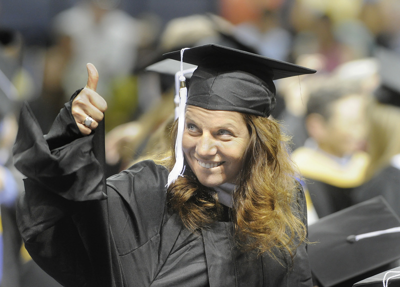 Susan Marean, of Gorham, gives a thumbs up to family and friends after receiving her degree in social work at today's graduation ceremony for the University of Southern Maine at the Cumberland County Civic Center.