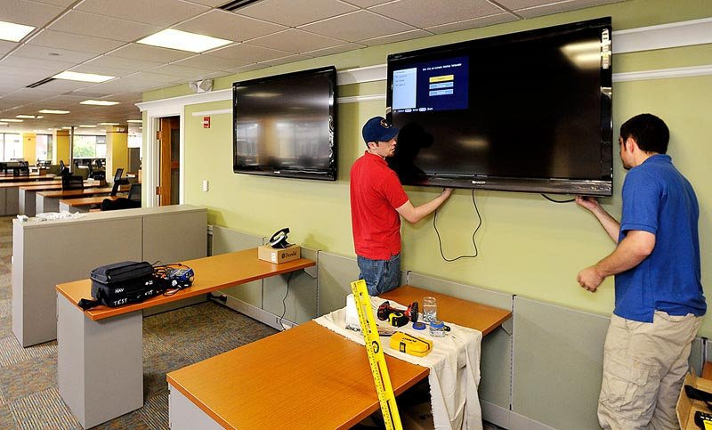 Nicholas Robertson and Alex Shupe, installation technicians for Headlight Audio Visual Inc., install a 60-inch Sharp HD flat screen TV, one of 19 flat screens installed throughout the MaineToday Media new headquarters at One City Center.