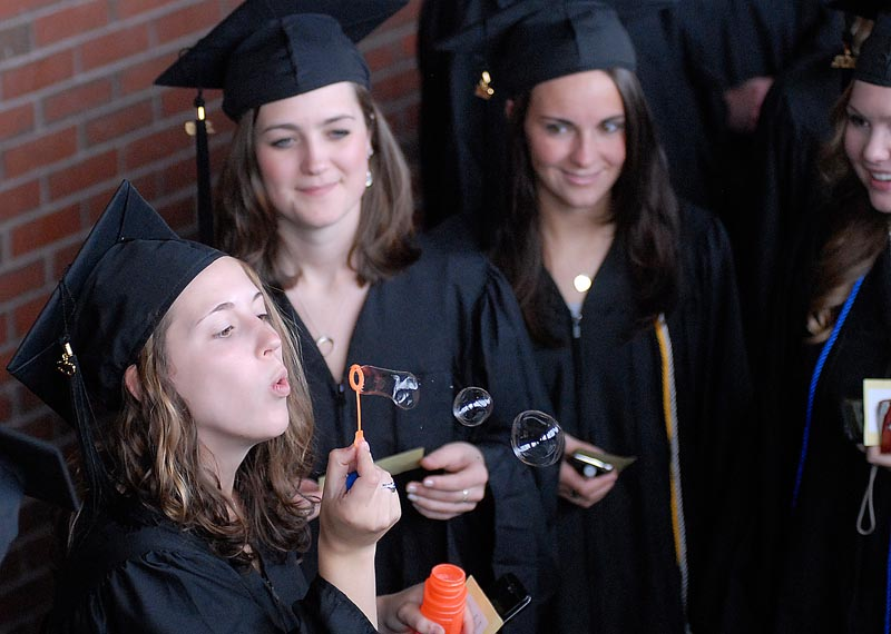 University of New England Graduate Margaret Thomas blows bubbles as she waits to enter the Cumberland County Civic Center for Commencement today.