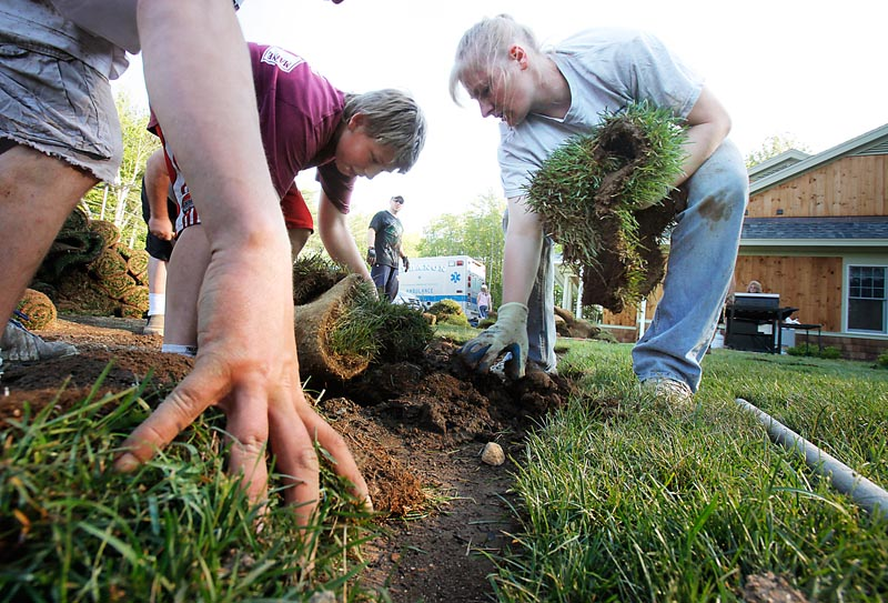 Kyle Sheriff, left, and Annette Thibodeau pull up a section of sod at the Lebanon Town Office on Monday. The sod, which recently had been laid down for the dedication of a monument to the town's Civil War soldiers, was damaged by vehicles driven over it Sunday. Tuckahoe Turf Farms donated the new sod, and volunteers replaced it Monday.