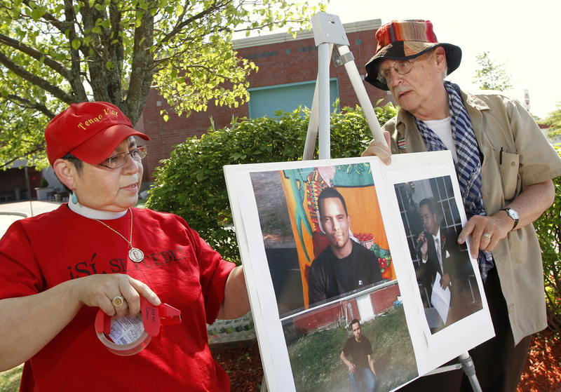 """The Rev. Virginia Marie Rincon and Wells Staley-Mays put up photos before the vigil. """"Selvin is not a criminal. We must make every effort to stay the deportation of this young man, who believed in the American dream,"""" Rincon said."""
