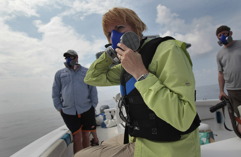National Wildlife Federation program manager Maura Wood, center, wears a mask as she and her colleagues examine oil floating on the surface of the Gulf of Mexico near the coast of Louisiana today.