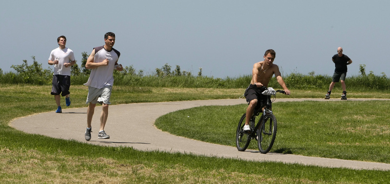 People enjoy the warm climate as they exercise on a path at Edgewater Park Monday in Cleveland. Northeast Ohio temperatures were in the 80's Monday and warm temperatures will continue throughout the week. An economist urged Maine business leaders to get behind federal climate change legislation.