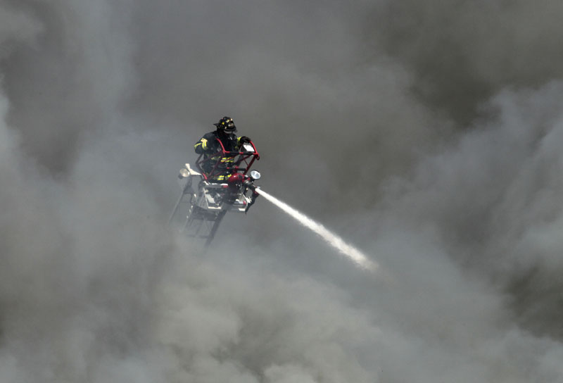Thick, black smoke billows around a firefighter on a ladder as he pours water on a three-alarm fire at the former Jordan Meats building today. The plant was in the process of being demolished.