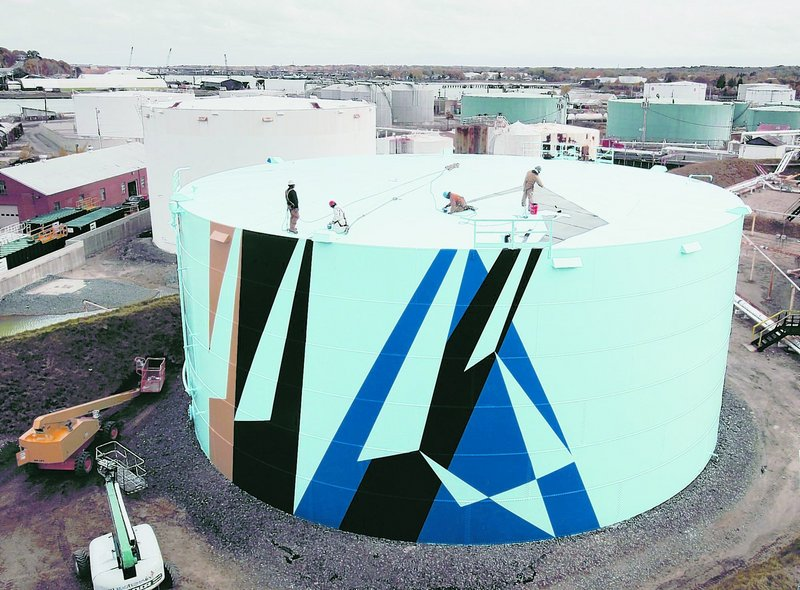 Workers paint the top of a tank last October at the Sprague Energy tank farm in South Portland. The project sends a sizable message about Maine's commitment to creativity.