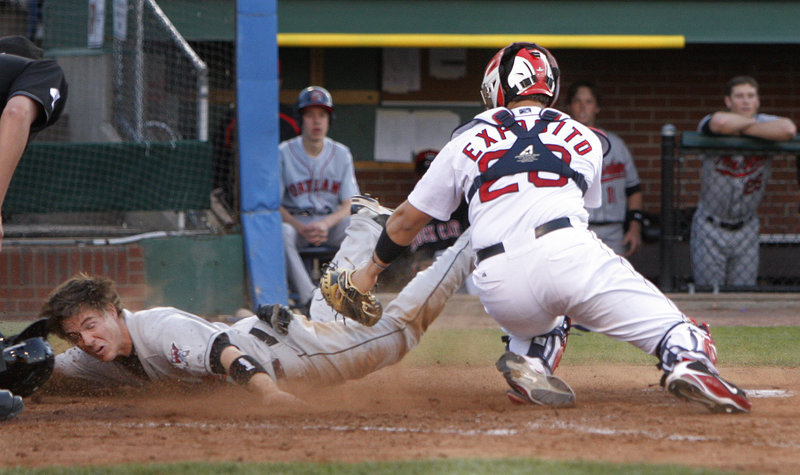 Joe Benson of New Britain dives by Sea Dogs catcher Luis Exposito to score in the second inning Friday night at Hadlock Field. Portland won, 13-4.
