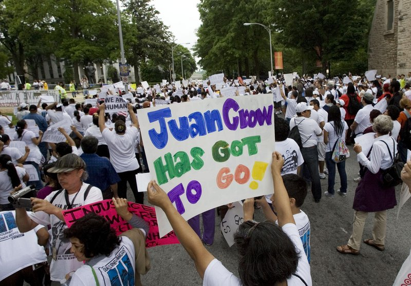 "Marcia Molina of Marietta Ga., holds up a sign that reads ""Juan Crow has got to go"" during an immigration rally Saturday in Atlanta. The sign refers to so-called Jim Crow practices that discriminated against American blacks."