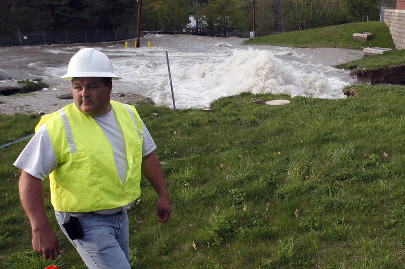 Water surges from the ground at the site of a water main break Saturday in Weston, Mass. Water to 700,000 households in Boston and more than two dozen suburbs is temporarily unsuitable for drinking after the break in a pipe that connects a major suburban reservoir to the city.