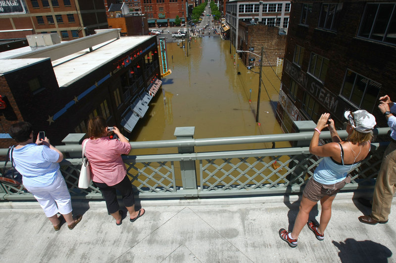 Spectators look at a flooded downtown street from over the Cumberland River on Monday in Nashville. About 1,500 guests were evacuated overnight from the Gaylord Opryland hotel.