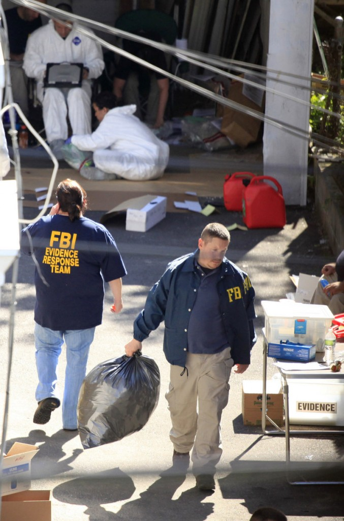 FBI agents remove evidence Tuesday from a house in Bridgeport, Conn. Investigators also served a search warrant at suspect Faisal Shahzad's home in Shelton, Conn., and visited a gun shop where he bought a rifle in March. Agents found a gun in a car used by Shahzad.