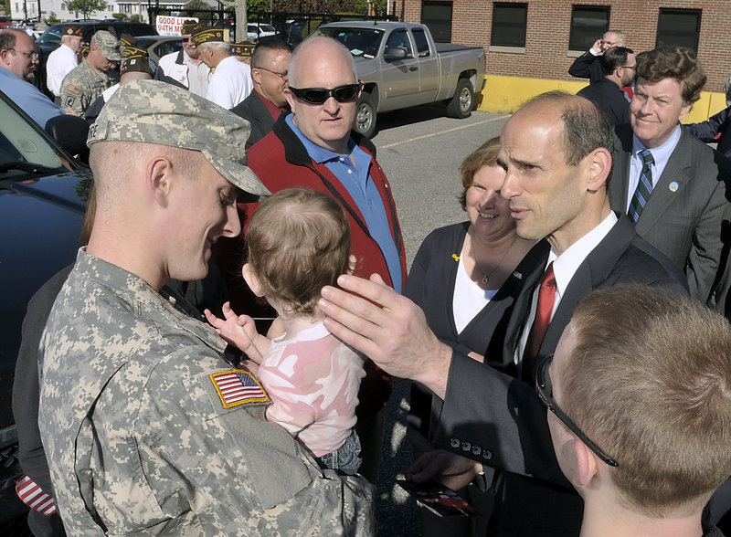 Gov. John Baldacci chats with Spc. Eric Madore and family as Army Reservists are given a grand send-off by family, friends and government officials Wednesday at the Army Reserve training center on Franklin Street in Saco. Behind Baldacci, Greg and Linda Madore enjoy the attention he is giving their son and the daughter of Eric's fiancee, 18-month-old Savanna. Also in the group of well-wishers are fiancee Katie Wildes, on Eric's left, and Adam Madore, 16, in right foreground. State Sen. Barry Hobbins watches at right.