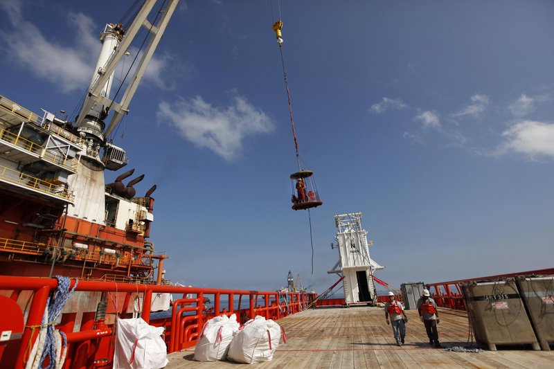 A worker is carried in a personnel basket from the Joe Griffin to the Q4000 in preparation to lower the containment vessel, seen in background, at the site of the Deepwater Horizon rig collapse in the Gulf of Mexico.