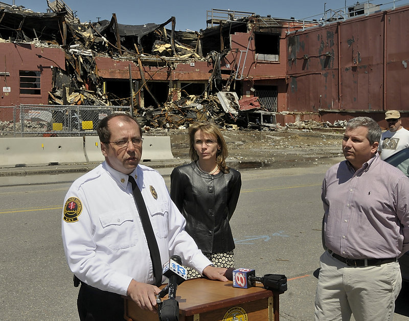 Portland Fire Chief Fred LaMontagne speaks Friday as Planning Director Penny Littell and Mark Woglom, a partner in a hotel and condo project on the old Jordan's Meats property, await their turn to take questions about Thursday's fire at the site.