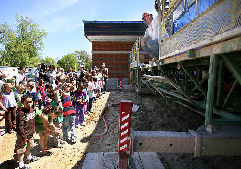 Delwin Berry of Maine Masonry demonstrates how a lift works Friday to Clifford Elementary School students at the new Ocean Avenue Elementary School in Portland. The students will be among those occupying the school when it opens.