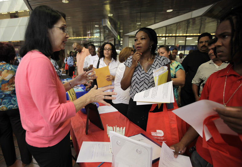 Nancy Rosello, left, an employment coordinator with Spectrum Programs Inc., talks with job seekers Thursday at a fair hosted by the Miami-Dade Community Action Agency in Miami. First-time claims for unemployment benefits dropped last week for the third straight time.