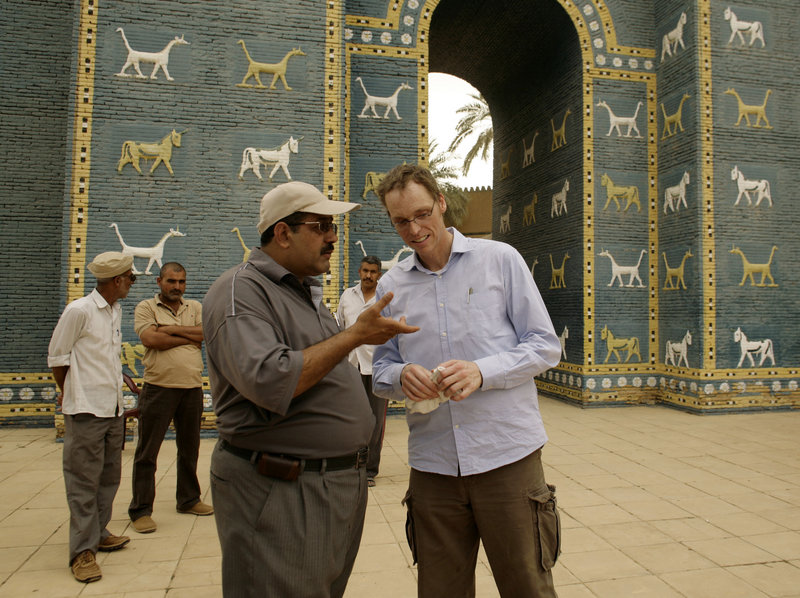 Jeffrey Allen, right, co-coordinator of a U.S.-funded project to restore the ancient city of Babylon, talks to guide Mohammed Taher outside a reproduction of the Ishtar gate at the site. Iraqi officials are at odds over keeping the site authentic or making money off it.