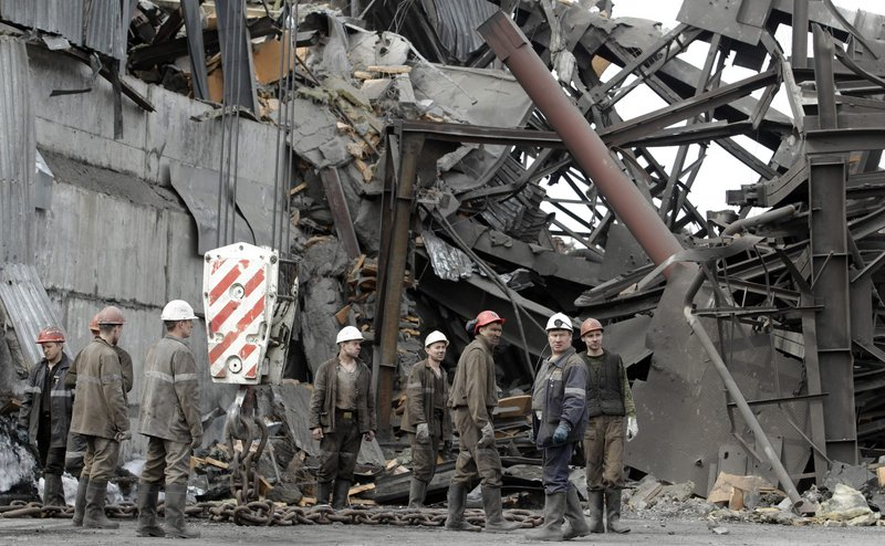 Emergency workers gather near the destroyed ventilation unit at the Raspadskaya mine, hit by explosions, in the city of Mezhdurechensk in the west Siberian region of Kemerovo, Russia, on Monday. The mine is Russia's largest underground coal mine in western Siberia.
