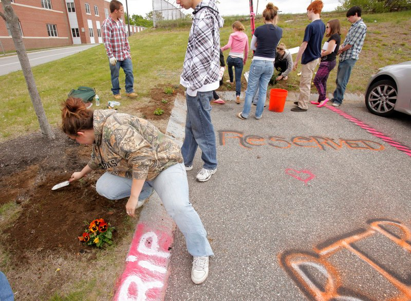 Ashley Morse, a senior at Scarborough High School, plants flowers Monday around a parking space at the school where senior Steven Delano always parked. Delano was killed in a car crash Saturday on his way to the Gorham High School prom with three other teenagers.
