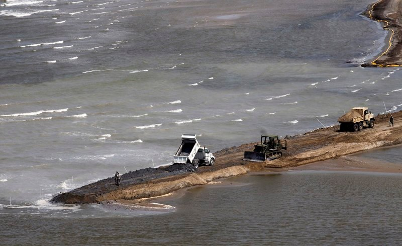 National Guard dump trucks, front-end loaders and backhoes dam off part of the marsh on Elmer's Island in Grand Isle, La., on Monday. Oil is still pouring into the Gulf of Mexico at a rate of about 210,000 gallons per day. At least 4 million gallons are believed to have leaked since an April 20 drilling rig explosion killed 11 workers.