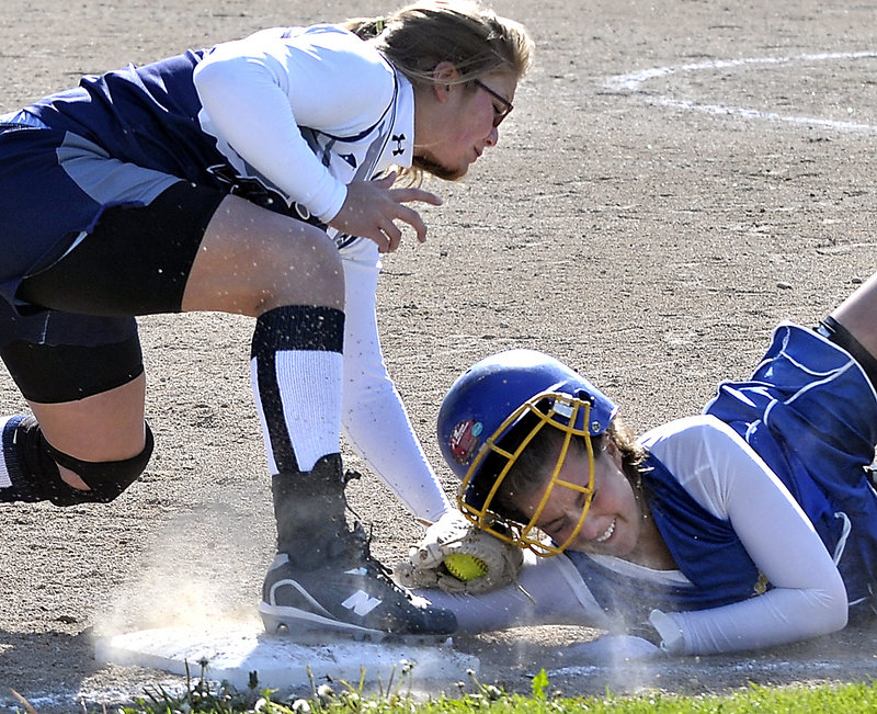 Poland third baseman Sara Sands tags out Falmouth's Alli Carver to complete a double play after a pop-up during their Western Maine Conference softball game in Falmouth. Falmouth won, 9-2.