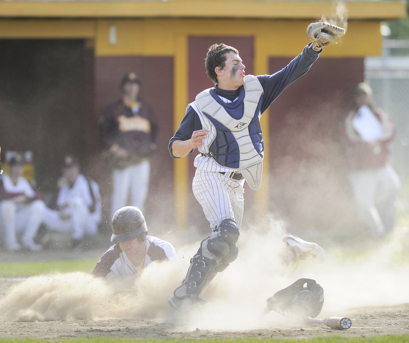Portland catcher Nick Volger takes the late throw as Steve Trask of Thornton Academy slides in Tuesday during Thornton's 10-2 victory at Saco. The Golden Trojans entered the game as the top-ranked team in Western Class A.