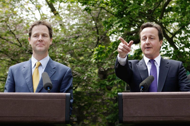 """Prime Minister David Cameron, right, and Deputy Prime Minister Nick Clegg hold their first joint news conference Wednesday in the garden of 10 Downing St. """"This is what the new politics looks like,"""" Clegg said."""