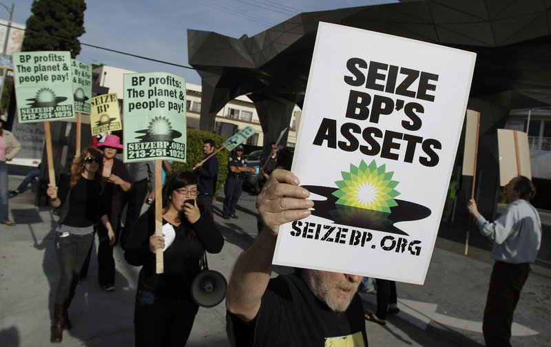 Protesters hold signs outside an Arco gas station during a rally against the Gulf oil rig disaster in Los Angeles on Wednesday. Investigators are trying to learn why proposed federal rules requiring additional measures to prevent spills were never enacted.