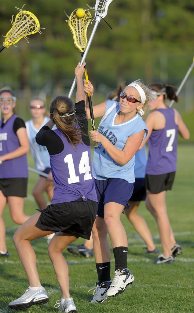 Katie Conley, right, of Westbrook fires a shot over Deering's Ursula Donovan to score a goal in the Blue Blazes' 6-5 win.
