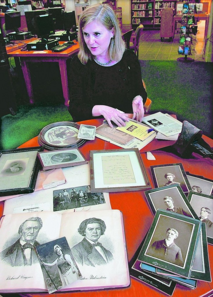 Sarah Sugden, director of the Waterville Public Library, arranges some of the materials, including documents and photographs, that have been discovered at the library during the renovation process.