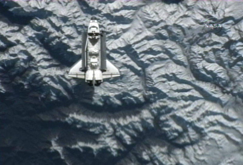 A frame grab taken from NASA television shows the space shuttle Atlantis flying over a mountainous region of Earth before docking at the International Space Station on Sunday.
