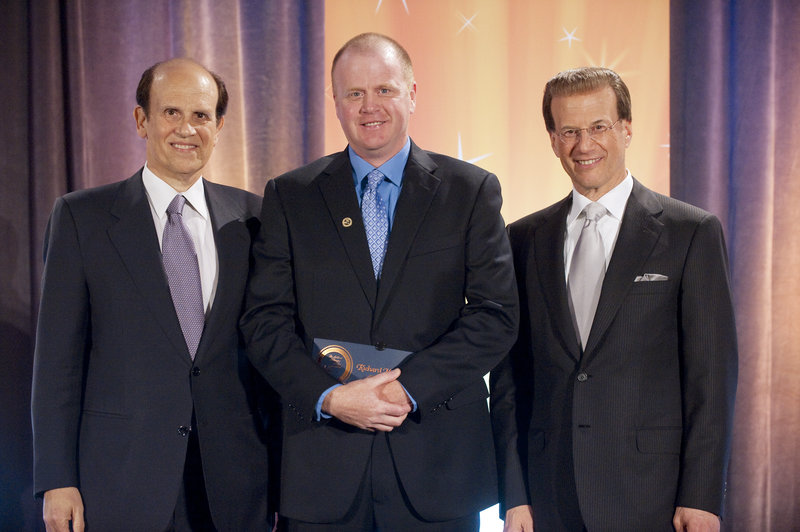 Milken Family Foundation co-founder Michael Milken, left, and foundation Chairman Lowell Milken, right, stand with The REAL School's Richard Meserve at the recognition ceremony Saturday in Santa Monica.