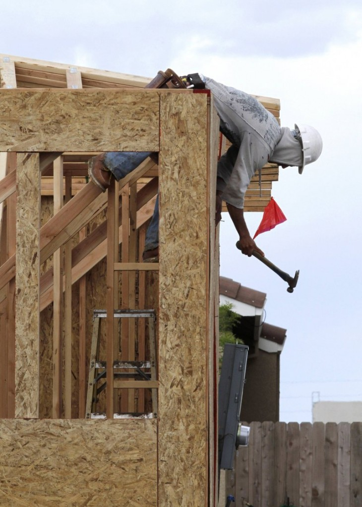 A construction worker hammers in exterior siding on a home under construction in Sacramento, Calif.
