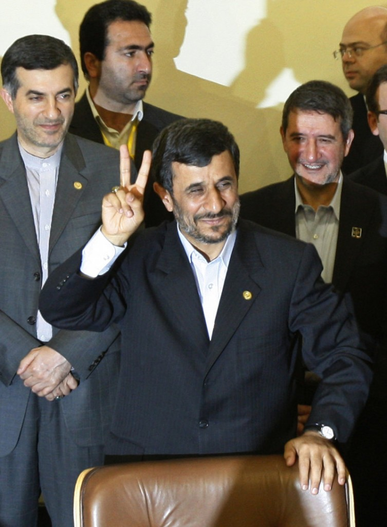 Iranian President Mahmoud Ahmadinejad flashes a victory sign Monday in Tehran before signing a pact to ship much of Iran's enriched uranium to Turkey.