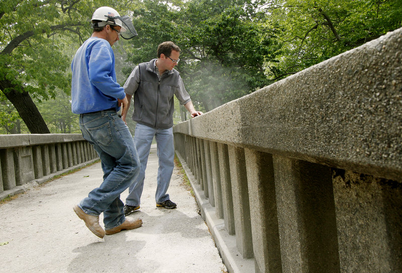 Scott Bourgoin, left, of Gorham-based Knowles Industrial Services, and Scott Hawk of Woodard & Curran in Portland discuss rehabilitation options for the footbridge in Portland's Deering Oaks on Tuesday.