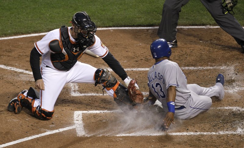 Alberto Callaspo of the Royals beats the tag by Orioles catcher Matt Wieters to score in the fifth inning Tuesday night in Baltimore. The Orioles won 4-3 in 10 innings.