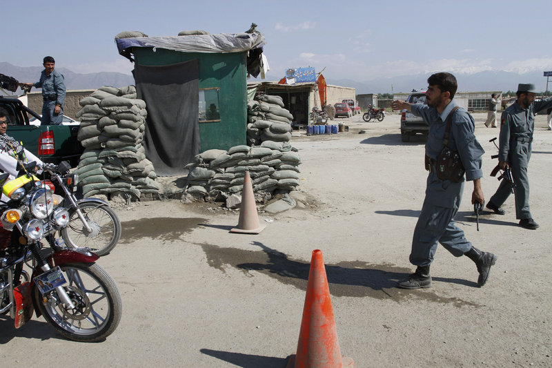 An Afghan police officer stops motorbikes Wednesday near the U.S.-run Bagram Airfield, where insurgents launched a brazen predawn assault with gunfire, rockets and grenades.