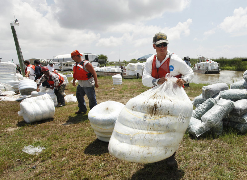 Workers load oil-absorbing material onto boats at the Louisiana Fish and Wildlife management area in Pass a Loutre, La., Wednesday. Oil from the Deepwater Horizon oil spill is beginning to infiltrate the coast of Louisiana, which is considered especially fragile because it is very marshy and difficult to decontaminate.