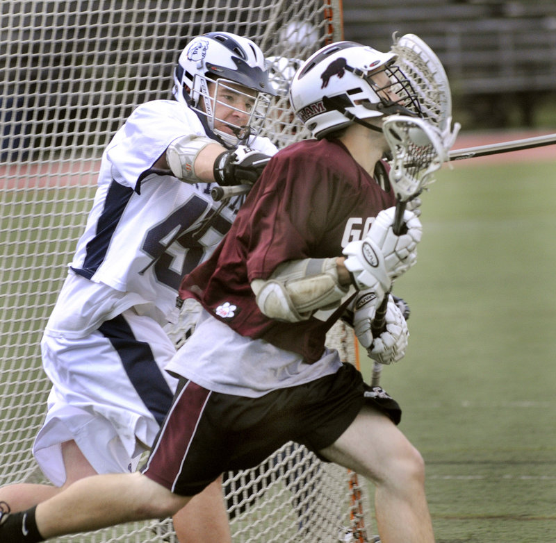 Luc Robitaille, right, of Gorham cradles the ball as he's chased by Portland's Eddie Walsh during Wednesday night's game. Robitaille scored for the Rams in an 18-4 loss.