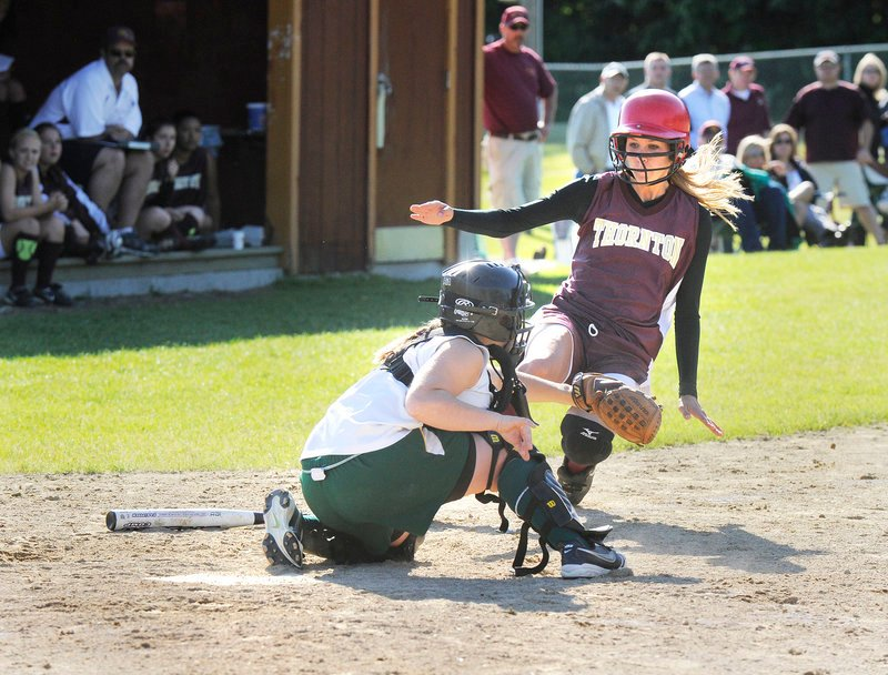 McAuley catcher Amber Libby blocks home plate and takes a throw before tagging out Molly Wiggin, one of two Thornton runners thrown out at the plate in the Trojans' 11-10 win Friday.