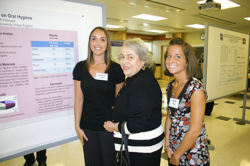 Past UNE President Sandra Featherman chats with recent dental hygiene graduates Stephanie Fortier and Ansley O'Bar, who presented their research about autism's impact on dental hygiene.