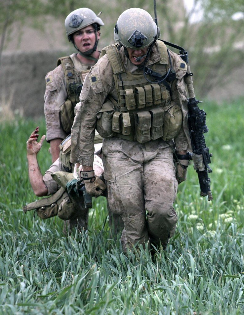 U.S. Marines carry a wounded fellow Marine across a field to a waiting Army Task Force Pegasus medevac helicopter during a firefight in Helmand province in Afghanistan.