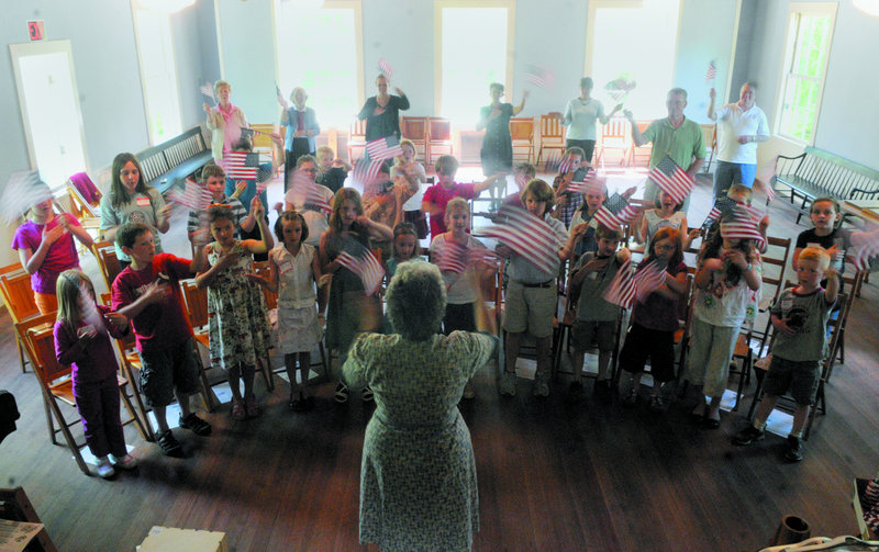 """Bonnie Wilder leads children in flag-waving choreography as they sing """"It's a Grand Old Flag"""" on Thursday in the old North Wayne School. Two groups of Wayne Elementary School students stepped back into May 1945 at the school this week."""