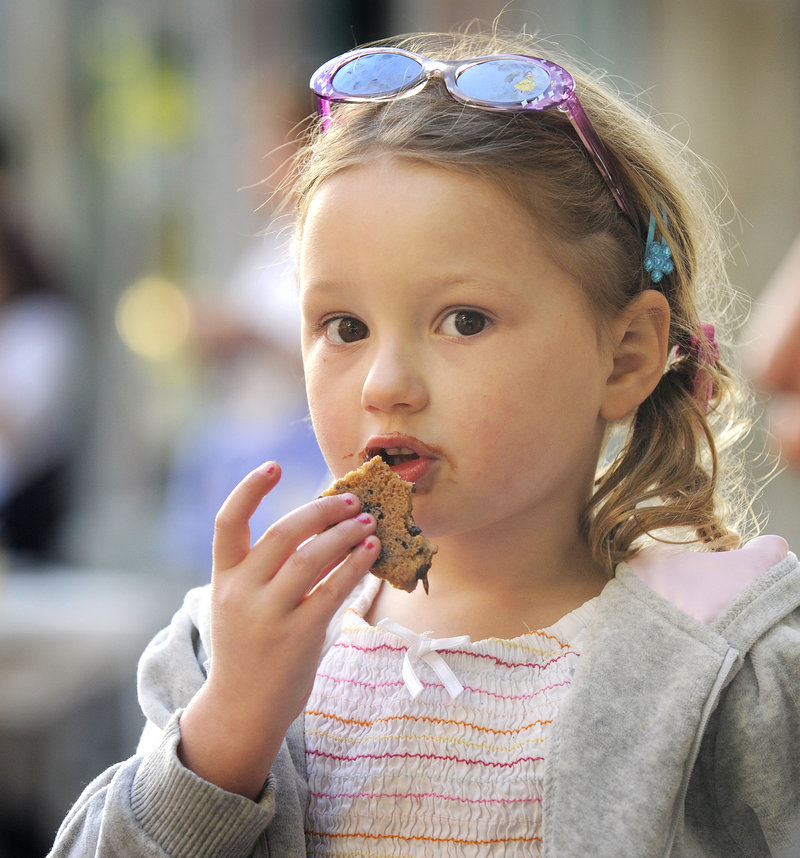 Three-year-old Isabelle Litalien of Belgrade enjoys a piece of a cookie pizza made by the Sweet Love shop during Hogs, Pies and Fireworks on Friday in Gardiner.