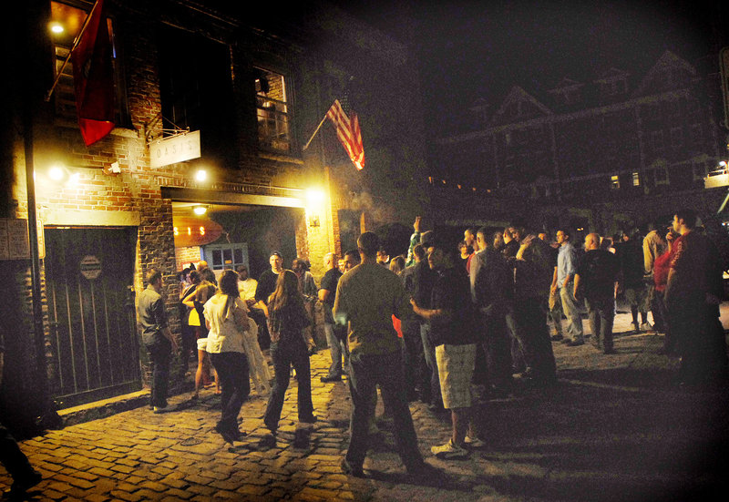 A crowd builds just outside Oasis on Wharf Street in the Old Port as patrons flow into the streets after closing time early Saturday morning.