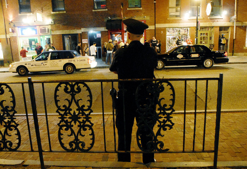"Portland Police Officer Evan Bomba watches the action in the Old Port on Friday night from his perch on Fore Street. ""Having these guys here makes you feel better,"" said one young woman as she walked by."