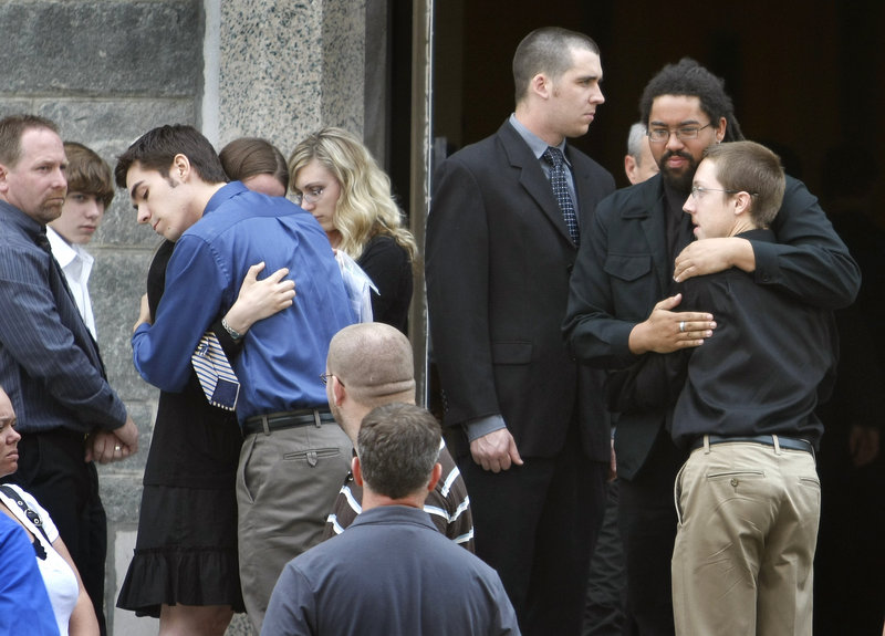 Friends and family console each other at the funeral for Eric Benson at St. Hyacinth's Church of St. Anthony's Parish in Westbrook on Saturday. Police have charged William Googins, 20, with manslaughter in the early May 23 attack in Portland's Monument Square.