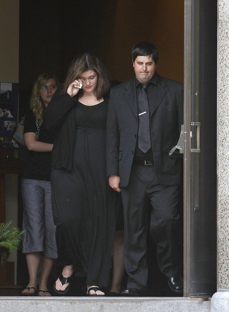 Andrew Benson and other mourners exit St. Hyacinth's Church in Westbrook following the funeral for his twin brother, Eric Benson, on Saturday.