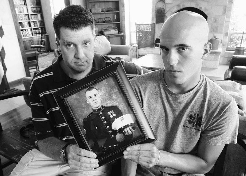 Jonathan Leicht, left, and Jesse Leicht hold a photo of their brother, Marine Cpl. Jacob Leicht, on Saturday in Kerrville, Texas. Jacob Leicht was killed in Afghanistan on Thursday.