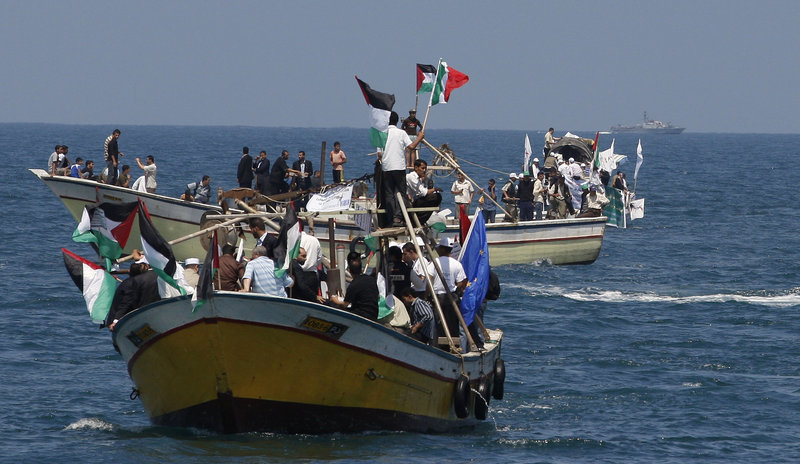 """Palestinians ride boats in Gaza waters while an Israeli navy vessel, seen in the background, patrols at a distance. The flotilla of vessels is intent on delivering humanitarian aid to Gaza, while Israel insists the vessels turn back or face """"necessary measures' to enforce the blockade."""