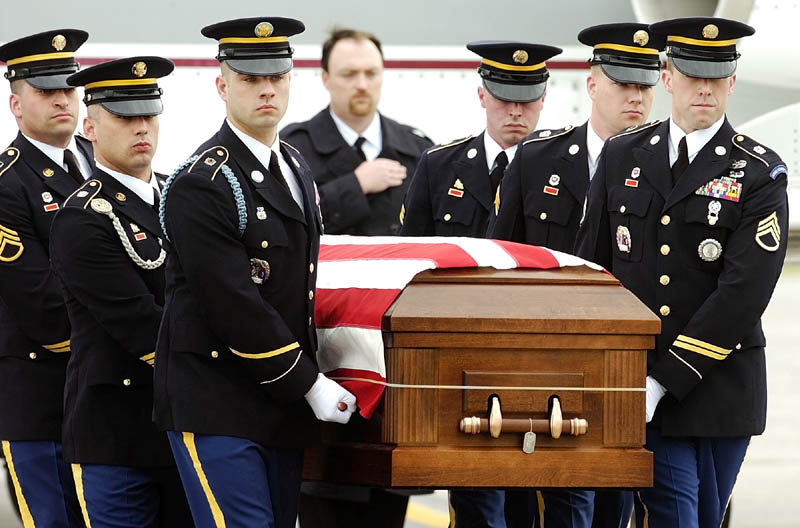Staff photo by Joe Phelan Maine Army National Guard soldiers move the casket containing U.S. Army Spc. Wade A. Slack's remains from a Falcon 20 charter jet to a waiting hearse Friday morning at the Augusta State Airport. The motorcade then drove north to Waterville. sidney